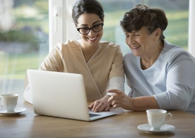 Smiling assistant teaching elderly woman