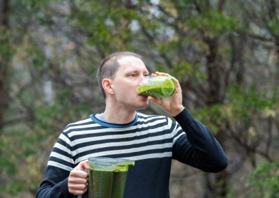 Young man standing outside, outdoors, holding plastic blender container, drinking from glass green smoothie made from vegetables, greens