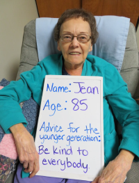 Older lady named Jean, holding a sign with her advice to 'be kind'